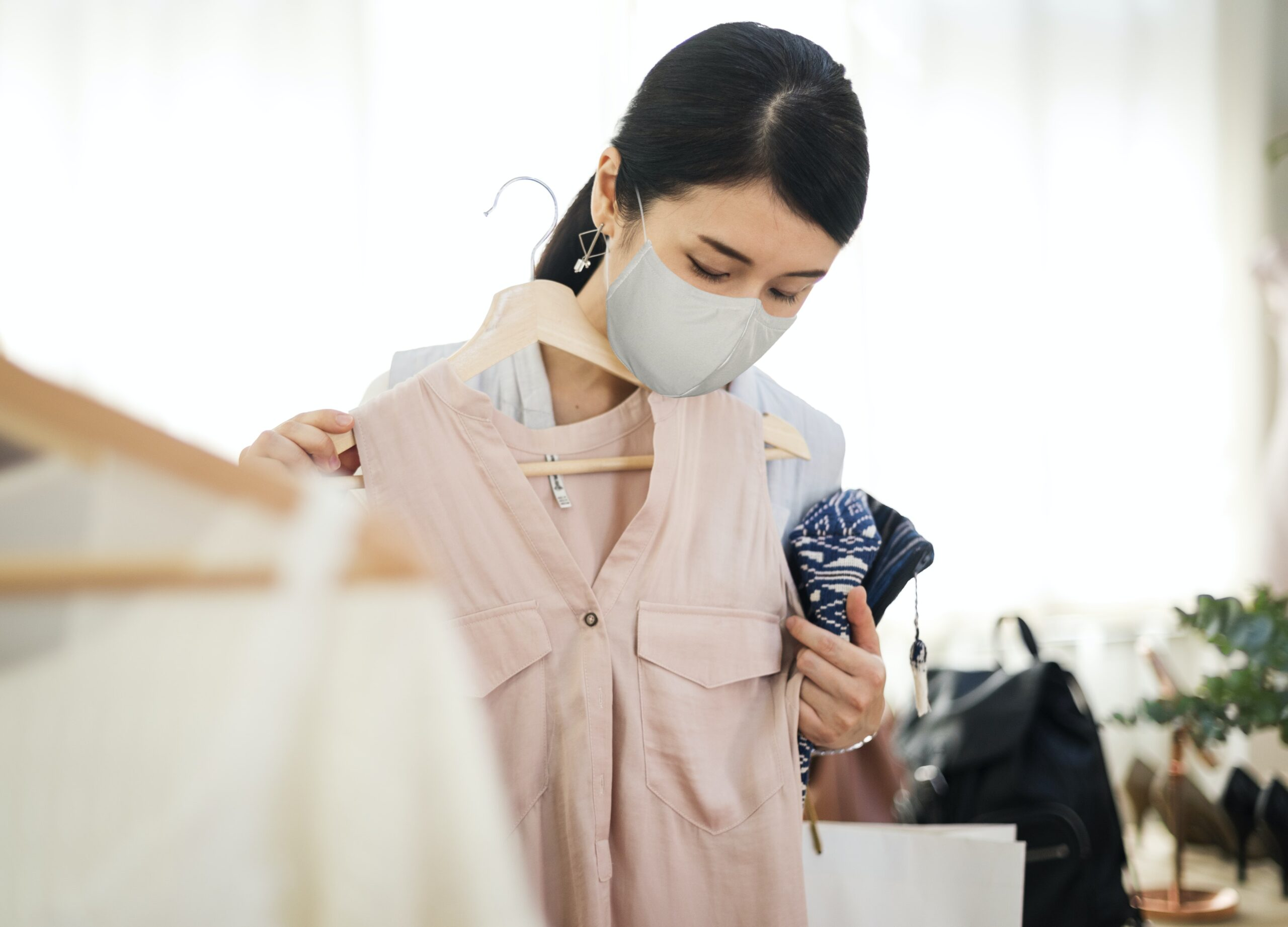 woman in mask shopping clothes